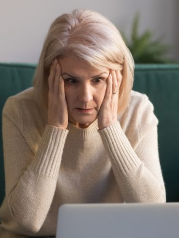 surprised senior old lady looking at laptop amazed by unexpected stuck computer problem sit on sofa at home