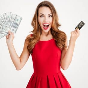 Closeup portrait smiling woman in red dress with credit cards in one hand and cash in other isolated on a white background